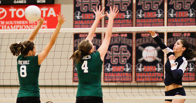 The Minutemen's Jackie Strople (8) spikes the ball past the outstretched arms of the Bearcats' Lauren Mierke and Danielle Lines (4) during a CIF Playoff volleyball match between the Maranatha High School Minutemen and the visting Bonita High School Bearcats in Pasadena, CA on November 14, 2009.  (STAR/TRIB/Correspondent photo by David Thomas/SPORTS)