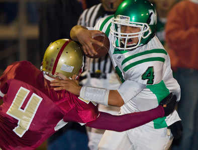Wildcats' Nick Bueno (4) runs through a tackle by Spartans' Scott Stetson (4) for a touchdown during a football game between the La Canada High School Spartans and the visiting Monrovia High School Wildcats in La Canada, CA on November 6, 2009.  (STAR-NEWS/Correspondent photo by David Thomas/SPORTS)