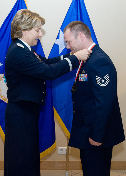 United States Air Force Maj. Gen. Michelle D. Johnson, Deputy Chief of Staff, Operations and Intelligence, SHAPE, Belgium presents Tech. Sgt. Joshua E. Watts, 424th Air Base Squadron, Chievres Air Base, Belgium with his medallion prior to the Annual Air Force Awards Banquet on SHAPE Feb. 22. Watts was nominated for NCO of the Year. (NATO photo by U.S. Army Sgt. 1st Class VeShannah J. Lovelace)