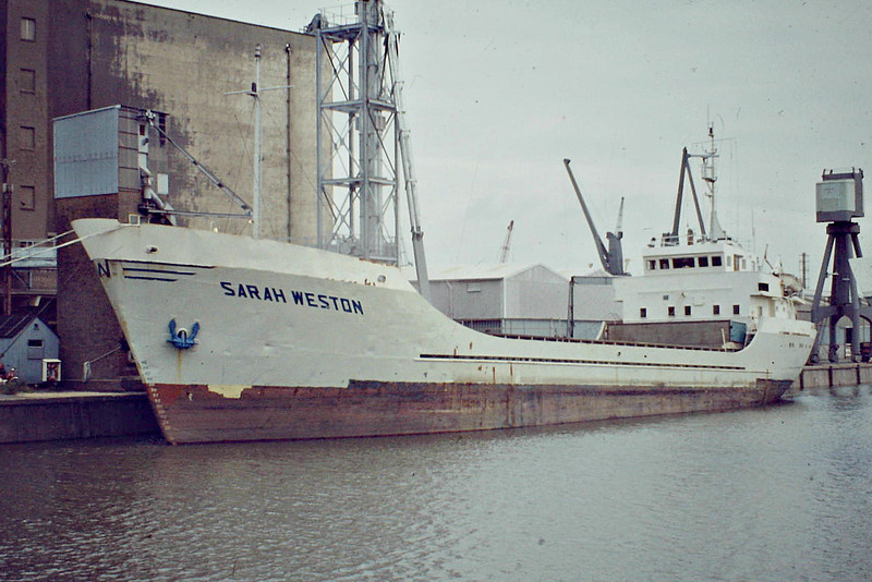 SARAH WESTON (London) - IMO7409372 - Cargo - GBR/1519/75 Scheeps Gebr Coops, Hoogezand, No.265 - 65.7 x 10.8 - Mardorf Peach Ltd. - Boston, loading grain on a riverside berth, 08/82.