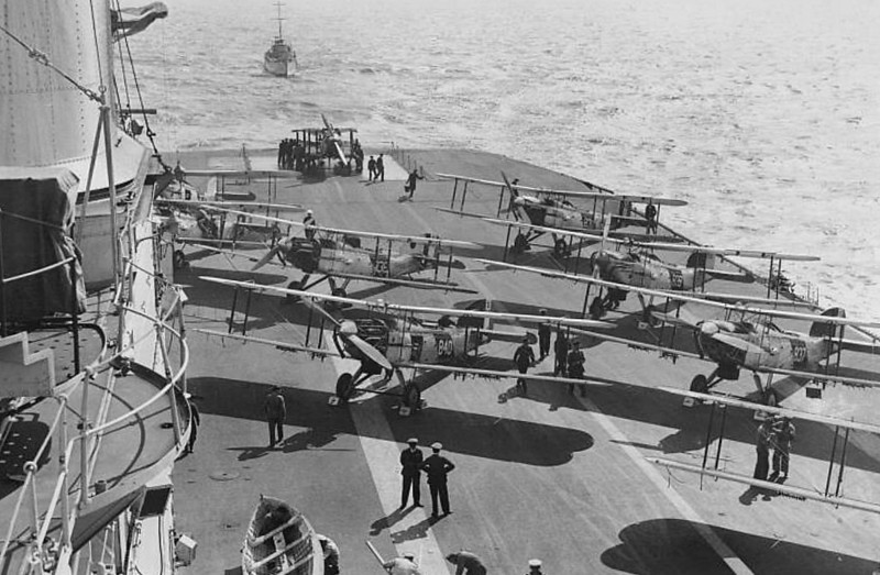1924 to 1942 - EAGLE (94) - Eagle Class Aircraft Carrier - 26800 tons - 203.5 x 32.0 - 1924 Armstrong Whitworth & Co., Elswick (1913 laid down as Chilean battleship ALMIRANTE COCHRANE, 1918 taken over by Admiralty and launched June 1918, completed as aircraft carrier) - 9 x 1 - 6in., 4 x 1 - 4in. QF, 25 aircraft (Nightjar, Plover, Flycatcher fighters, Panther, Walrus, Bison, Blackburn recon planes, Dart torpedo bombers) - 22.5 knots - 1927 1 x 1 - 4in.QF, 14 x 1 - 7.7mm added, 1929: 2 x 1 - 40mm added, 1932 1 x 8 - 40mm, 2 x 4 - 12.7mm added, 1937: 1 x 8 - 40mm added, 1942: 12 x 1 - 20mm added - 09/1939 18 Swordfish, 06/1942 16 Sea Hurricane - 08/39 China Station, 09/39 to Colombo and East Indies Squadron, patrols in Indian Ocean, 14/03/40 explosion in bomb room, 14 dead, 3 badly injured, 16/03/40 arrived Singapore, bombs landed, drydocked for repair, 27/05/40 Mediterranean Fleet, 10/07/40 ship's a/c sank destroyer LEONI PANCALLO, Augusta, Sicily, 22/08/40 ship's a/c sank submarine IRIDE and depot ship MONTE GARGANO, 05/11/40 after months of sustained air attacks, hull found to be damaged and sent for repairs, 16/11/40 returned to service but again under repair all of December, 08/04/41 replaced by HMS FORMIDABLE, to return to UK via Cape, 06/41 operating patrols from Freetown, 06/11/41 ship's a/c sank blockade runner, 01/11/41 Liverpool for refit, ELBE off Azores, 02/42 returned to service, to Force H Gibraltar, 03/42 two aircraft delivery trips to Malta, 05/42 two more aircraft delivery trips to Malta, 11/06/42 Force W, escorting resupply convoy to Malta, 17/06/42 returned to Gibraltar, 14/07/42 aircraft delivery trip to Malta, 10/08/42 joined escort group for Operation Pedestal to Malta, 11/08/42 torpedoed and sunk by U73 south of Majorca, sank in 8 minutes - seen here with Fairey IIIF's ranged on the afterdeck in the 1930's.