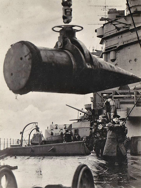 BRINGING A PROJECTILE ABOARD - Hoisting a 16 inch shell aboard a Nelson Class battleship. These were the biggest shells in use in the Royal Navy, weighing just under a ton and just under 6 feet long. The Nelson Class ship could throw these monsters for 42000 yards and they could penetrate 14 inches of armour at 15000 yards. It was the destructive power of these shells that largely brought about the destruction of the BISMARCK once she had been slowed down enough for poor old HMS RODNEY to catch her up. She fire 340 of these shells at the German ship, one of which blew 'B' turret to pieces.