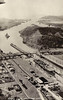 A US Navy Escort Carrier enters the Miraflores Locks, apparently engaged on transport duties, followed by a battleship,
