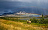 CANADIAN ROCKIES - JASPER NATIONAL PARK.  A male elk with full antlers grazing in front of a lake and mountain range with a double rainbow in the background. [ELK_7746]