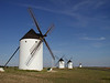"""Perhaps the most iconic feature of La Mancha, these windmills, or <i>molinos de viento</i>, were made famous by Miguel de Cervantes in his novel <i>Don Quijote de la Mancha</i>.  They may not be able to transform into giants, as feared by our befuddled knight hero, but they are a testament to the omnipresent winds that tear across the <i>llano</i>.  <div id=""""caption_tourlink"""" align=""""right""""> [photo by Chris Benesh]</div>"""