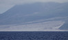 """The old lava flow with large boulder debris from the Montserrat Volcano eruption of 1997 — the volcano looms under cloud cover in the background. Jesse took this photo from the ferry looking towards the eastern side of the island, where the old airport was located.<div id=""""caption_tourlink"""" align=""""right""""> [Photo © guide Jesse Fagan]</div>"""