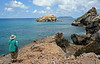 """Participant Hiroko Keith takes some time to sketch the scenery after enjoying views of nesting Bridled Terns on the distant rock. This is the peninsula at the end of Pointe des Chateaux on Guadeloupe; the island of Desirade can be seen in the far back. <div id=""""caption_tourlink"""" align=""""right""""> [photo © guide Alvaro Jaramillo]</div>"""
