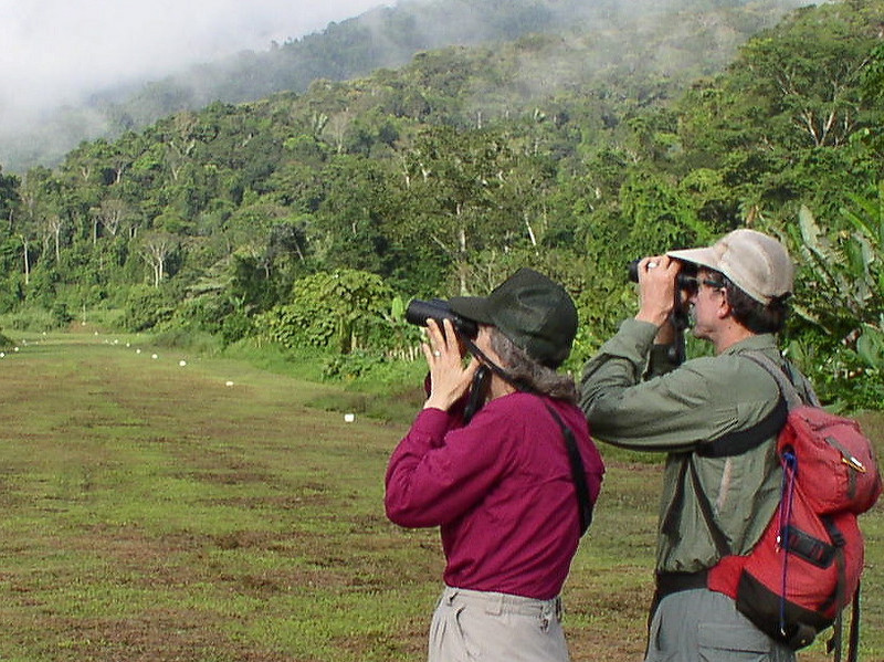 """Participants Jim Logan & Sherry Lewis birding the Cana airstrip <div id=""""caption_tourlink"""" align=""""right""""> [photo © guide John Coons]</div>"""