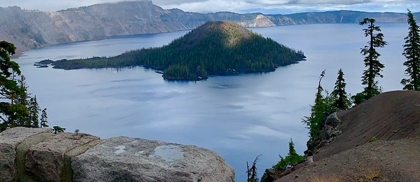 One of Oregon's great treasures is Crater Lake National Park. Crater is the deepest lake in the United States at 1949 feet (594 m) deep. Its clear, deep blue color makes it a favorite of artists and tourists alike, and birds abound in the surrounding landscape, where peaks in the Cascades rise to over 10,000 feet (3050 m). The lake was formed about 7700 years ago when a volcano collapsed; such formations are known as calderas. This is a view toward Wizard Island, a volcanic cinder cone within the lake. (Photo by participant Mona Gardner.)