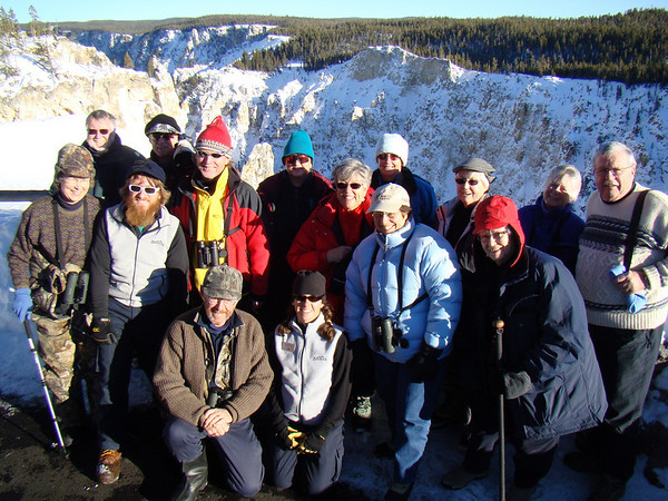 "With amazing landscapes and great wildlife experiences, it's easy to be happy!  Here's our 2009 group for a portrait at the Grand Canyon of the Yellowstone on another beautiful day, with our two snowcoach drivers. <div id=""caption_tourlink"" align=""right"">[photo © Jan Pierson]</div>"