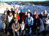 """With amazing landscapes and great wildlife experiences, it's easy to be happy!  Here's our 2009 group for a portrait at the Grand Canyon of the Yellowstone on another beautiful day, with our two snowcoach drivers. <div id=""""caption_tourlink"""" align=""""right"""">[photo © Jan Pierson]</div>"""