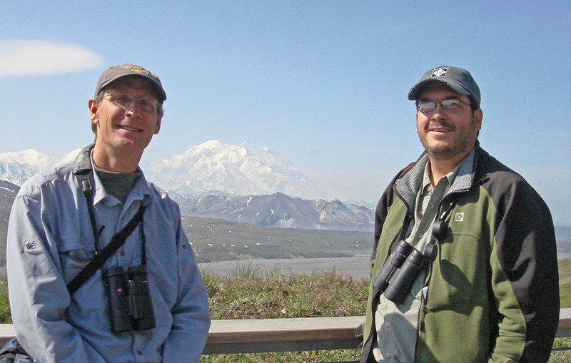"Chris Benesh (l.), aka the ""Solitaire,"" and George Armistead, aka the ""Owl,"" at the ready to sell you a used car!  No, no, wait, my bad...let's see, hmmm, Chris, George, a huge mountain in the background in June...it must be Alaska!  And a sunny day in front of Denali at that...wow!"