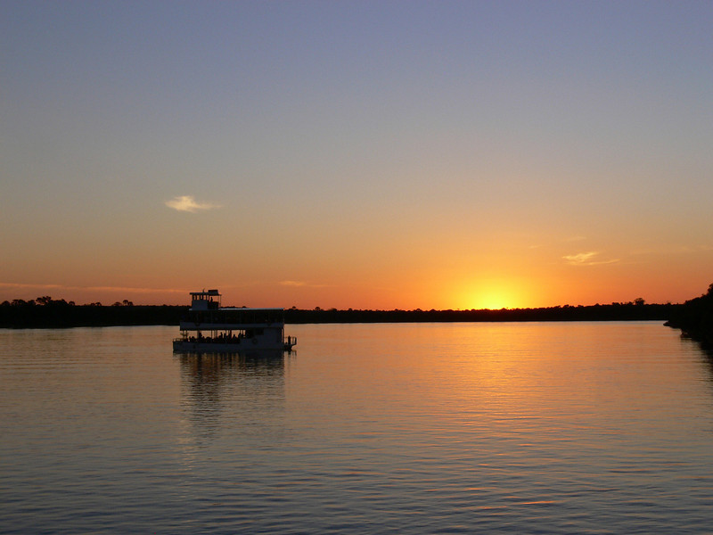 """Sunset at the tail end of a sundowner cruise on the famous Zambezi River, along which lie famous Victoria Falls.<div id=""""caption_tourlink"""" align=""""right"""">Link to: <a id=""""caption_tourlink"""" href=""""http://www.fieldguides.com/malawi.htm"""" target=""""_blank"""">ZAMBIA & MALAWI</a><br>[photo © Marge Barrett]</div>"""