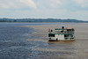 """A local boat crosses the """"meeting of the waters"""" near Manaus: the Rio Negro and the Solimoes (what Brazilians call the Amazon west of this juncture) run side by side for miles, slowing mixing to become the Rio Amazonas. Photo by participant Deborah Linde."""