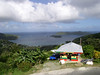 "Tobago is Trinidad's smaller neighbor island. The two comprise the nation, but they are quite different. Trinidad is big and bustling (in the urban areas), while Tobago is mellow, slow, and distinctly more ""Caribbean"" than Trinidad. More Caribbean? Well, these two islands are right at the interface between the Antilles and South America, and they are considered to have an avifauna allied more closely to South America than to the Caribbean. This is definitely true for Trinidad but, both in birds and culture, it is a little less true for Tobago. Here a colorful shop in the foreground, with the seabird island of Little Tobago in back. <div id=""caption_tourlink"" align=""right""> [photo © guide Megan Crewe]</div>"