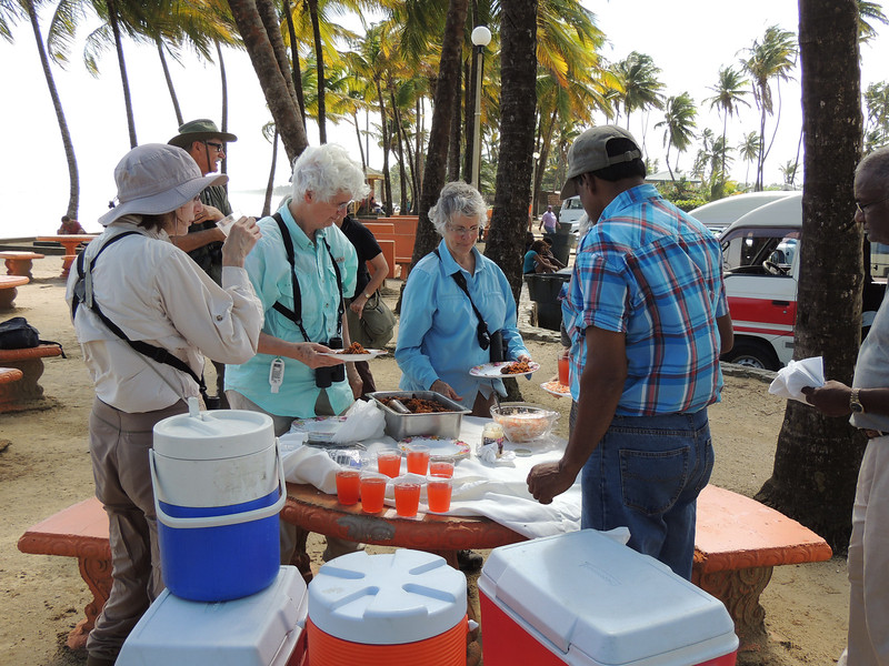 Lunch!  Local guides Mahase and Ramdass make sure everyone has what they need during a meal at Manzanilla Beach. (Photo by guide Megan Crewe)