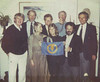 Famous faces. Note that the Wee Kiwi is barely taller than Sharon Green. - Mundle The flag was my proposed s.i.n.s. logo which was rejected in flavor of the rudderless Laser to indicate that this organization wasn't going anywhere. - Nerney This was at Kirby's house, probably 1980 - de