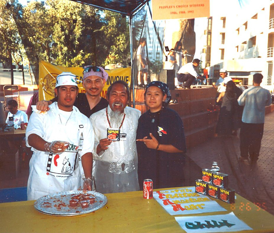 Uncle Roy Morales is holding a can of the SIPA secret ingredient for the Visual Communications Chili Cook-off Contest / Fundraiser in Little Tokyo. He is surrounded by SIPA staff members including long time counselor Gil Ayuayo standing behind.