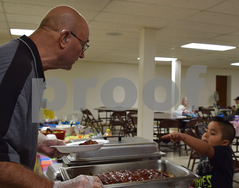 Jayden Hernandez of DeKalb, 6, (right) points to the slice of meatloaf he wants for lunch served by volunteer Bryant Irving during Summer Lunch and More on June 27. SLAM offers free lunch for the community and those in need from noon to 1 p.m. Tuesdays through Fridays until Aug. 4 at First United Methodist Church, 317 N. Fourth St. in DeKalb.
