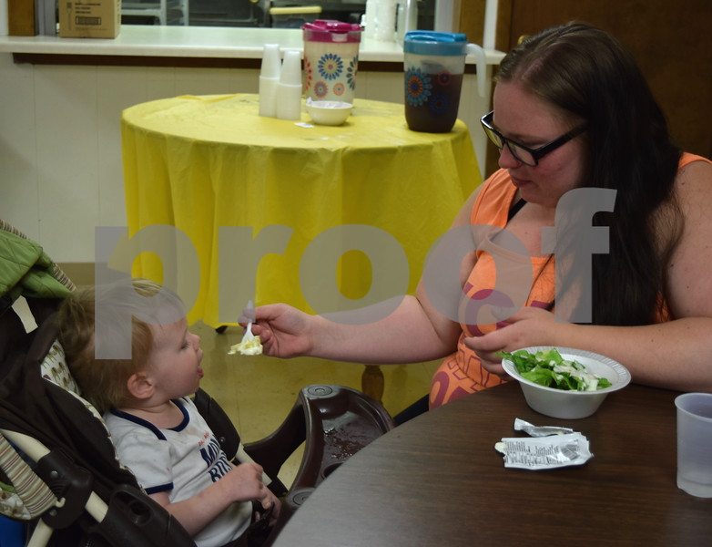 Shelby Beck of DeKalb feeds her 22-month-old son, Jack Ottolino, a salad during Summer Lunch and More on June 27. SLAM offers free lunch for the community and those in need from noon to 1 p.m. Tuesdays through Fridays until Aug. 4 at First United Methodist Church, 317 N. Fourth St. in DeKalb.
