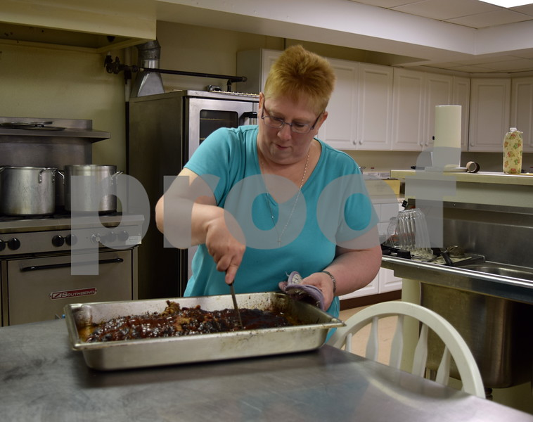 Chef Kathi West slices a meatloaf in the kitchen during Summer Lunch and More on June 27. West said as the program's chef, she creates healthy meals using budget-friendly recipes families can easily recreate at home.