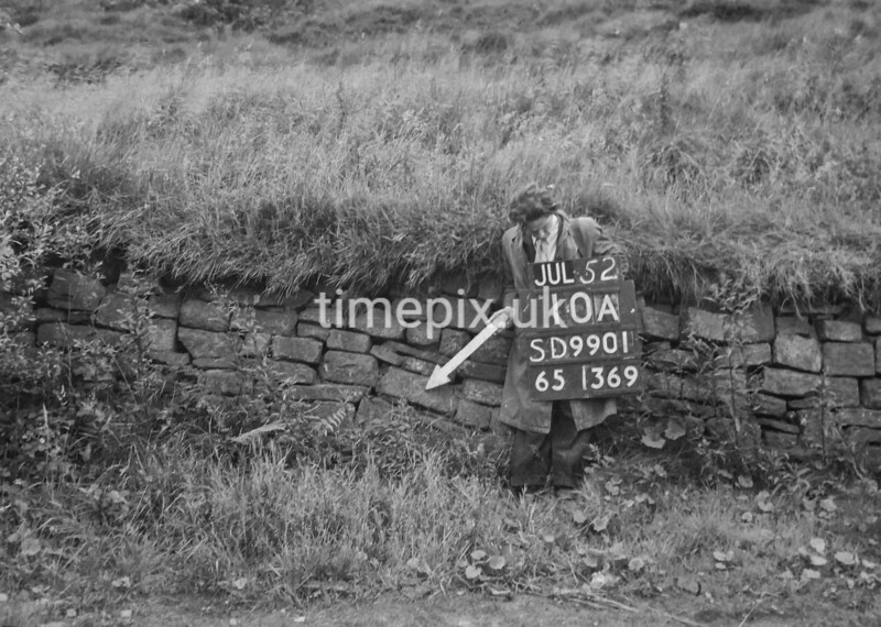 SD990110A, Man marking Ordnance Survey minor control revision point with an arrow in 1950s