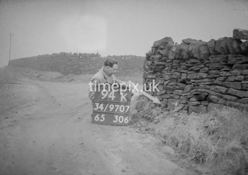 SD970794K, Man marking Ordnance Survey minor control revision point with an arrow in 1950s
