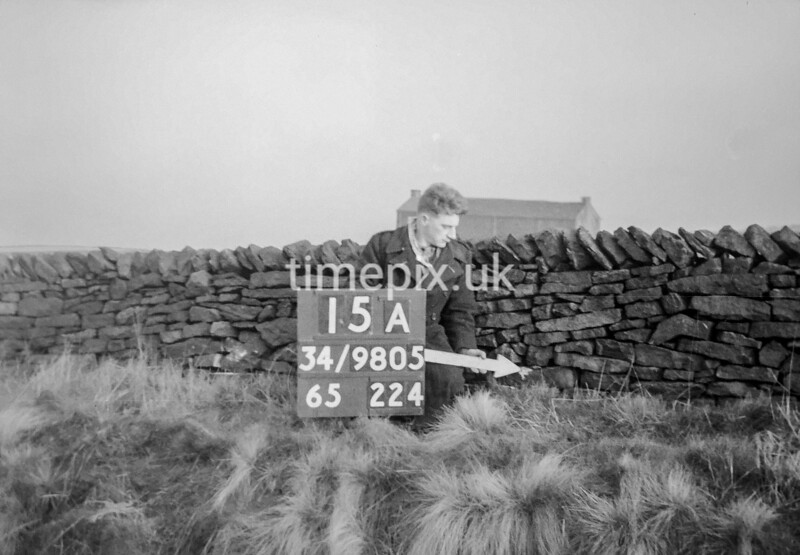 SD980515A, Man marking Ordnance Survey minor control revision point with an arrow in 1950s