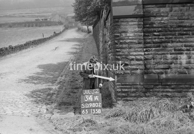 SD980234A, Man marking Ordnance Survey minor control revision point with an arrow in 1950s