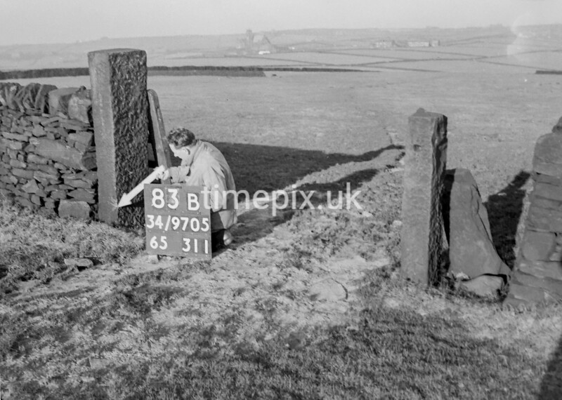 SD970583B1, Man marking Ordnance Survey minor control revision point with an arrow in 1950s