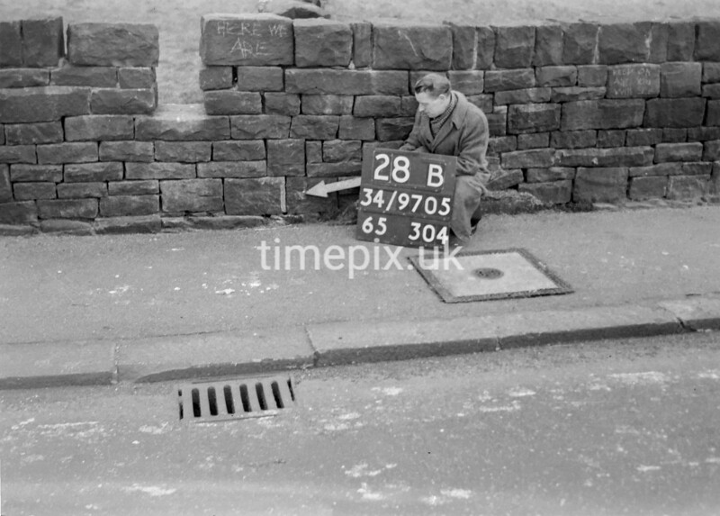 SD970528B, Man marking Ordnance Survey minor control revision point with an arrow in 1950s
