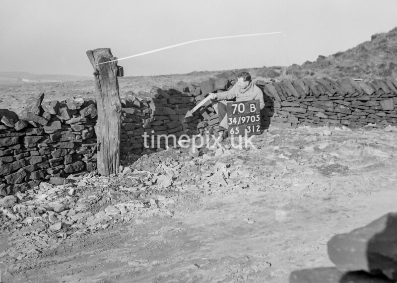 SD970570B, Man marking Ordnance Survey minor control revision point with an arrow in 1950s