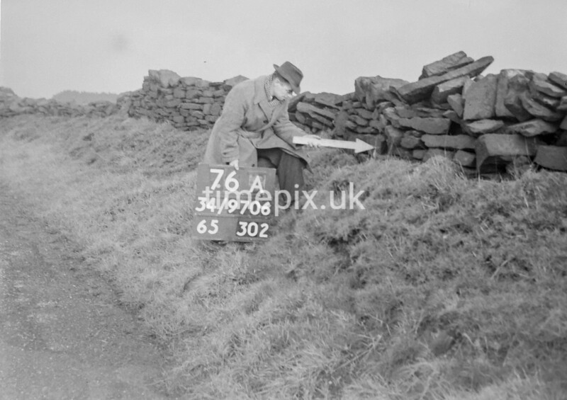 SD970676A, Man marking Ordnance Survey minor control revision point with an arrow in 1950s