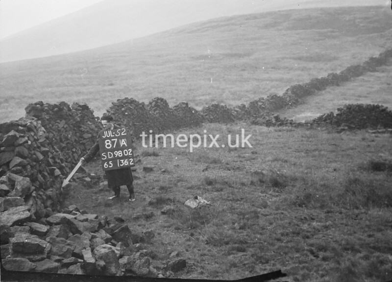 SD980287A, Man marking Ordnance Survey minor control revision point with an arrow in 1950s