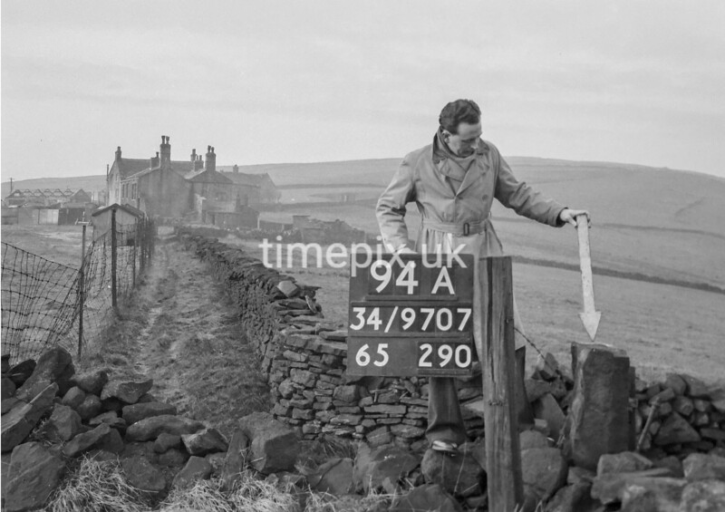 SD970794A, Man marking Ordnance Survey minor control revision point with an arrow in 1950s
