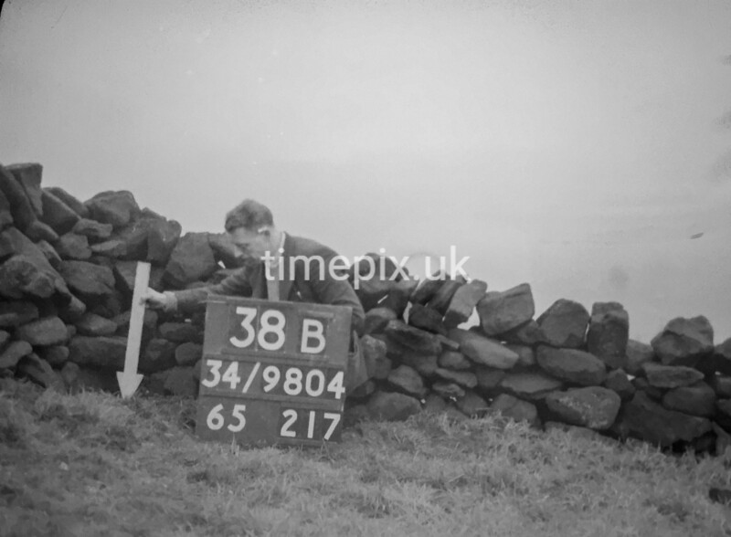 SD980438B, Man marking Ordnance Survey minor control revision point with an arrow in 1950s