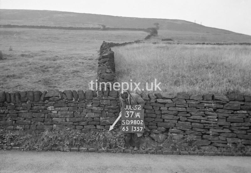 SD980237A, Man marking Ordnance Survey minor control revision point with an arrow in 1950s