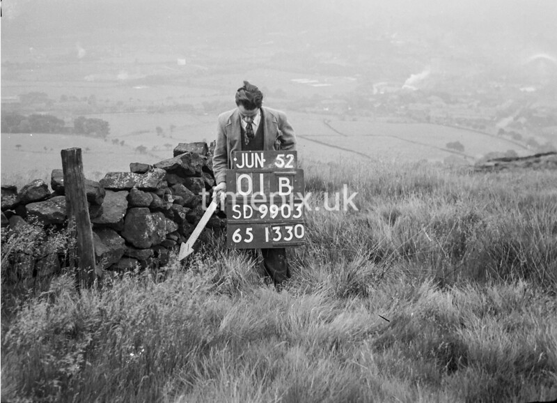 SD990301B, Man marking Ordnance Survey minor control revision point with an arrow in 1950s
