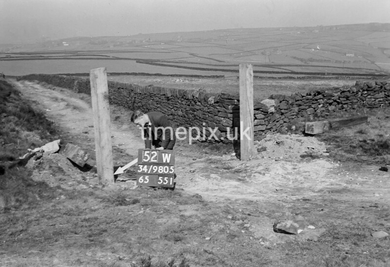 SD980552W, Man marking Ordnance Survey minor control revision point with an arrow in 1950s