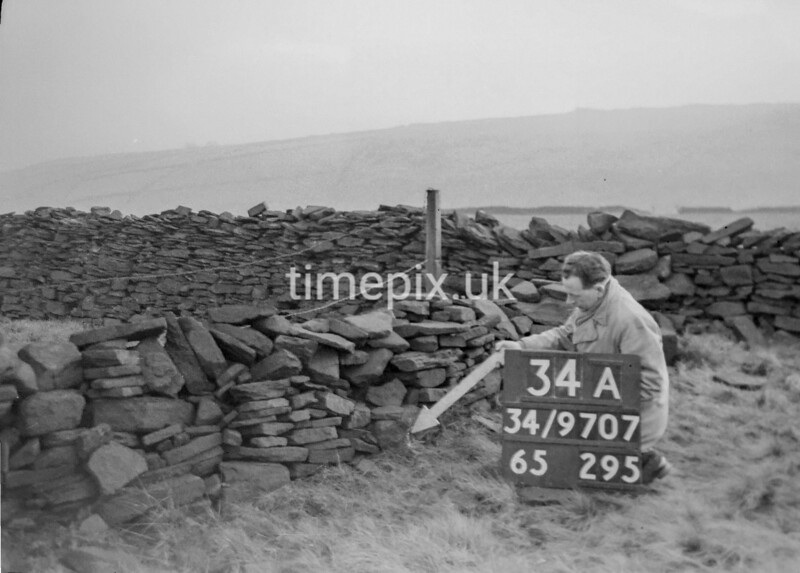 SD970734A, Man marking Ordnance Survey minor control revision point with an arrow in 1950s