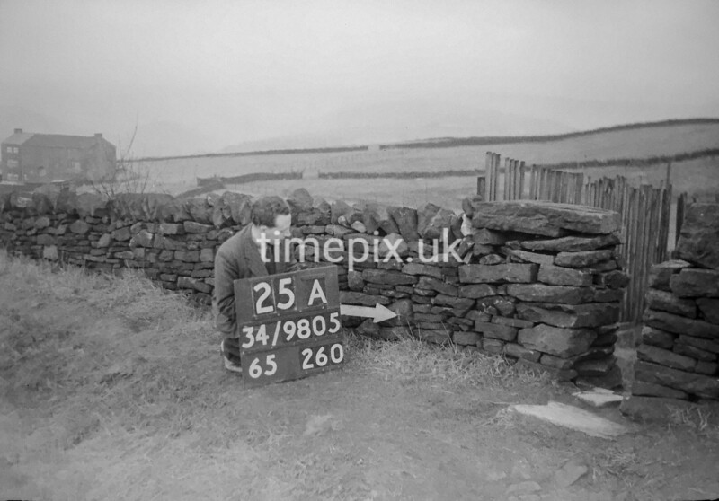 SD980525A, Man marking Ordnance Survey minor control revision point with an arrow in 1950s