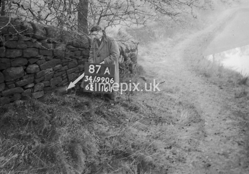 SD990687A, Man marking Ordnance Survey minor control revision point with an arrow in 1950s