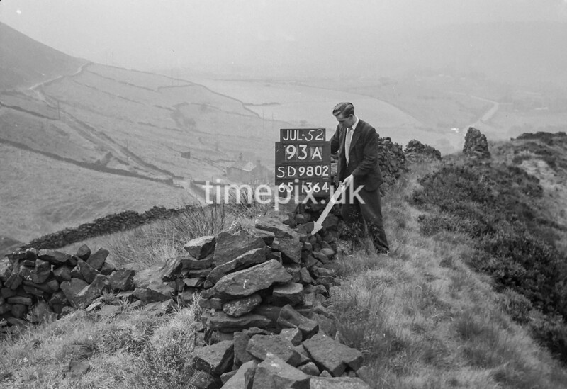 SD980293A, Man marking Ordnance Survey minor control revision point with an arrow in 1950s