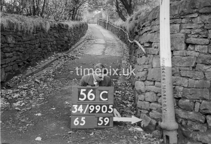 SD990556C, Man marking Ordnance Survey minor control revision point with an arrow in 1950s