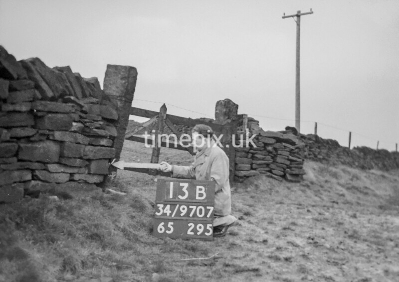 SD970713B, Man marking Ordnance Survey minor control revision point with an arrow in 1950s