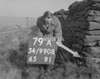 SD990879A, Man marking Ordnance Survey minor control revision point with an arrow in 1950s