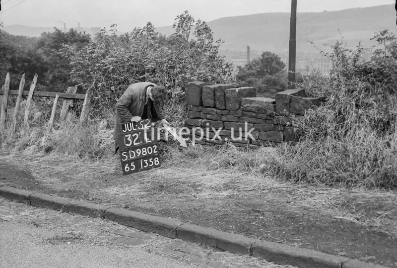 SD980232L, Man marking Ordnance Survey minor control revision point with an arrow in 1950s