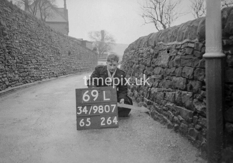 SD980769L, Man marking Ordnance Survey minor control revision point with an arrow in 1950s