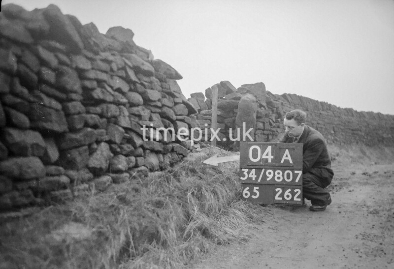 SD980704A, Man marking Ordnance Survey minor control revision point with an arrow in 1950s