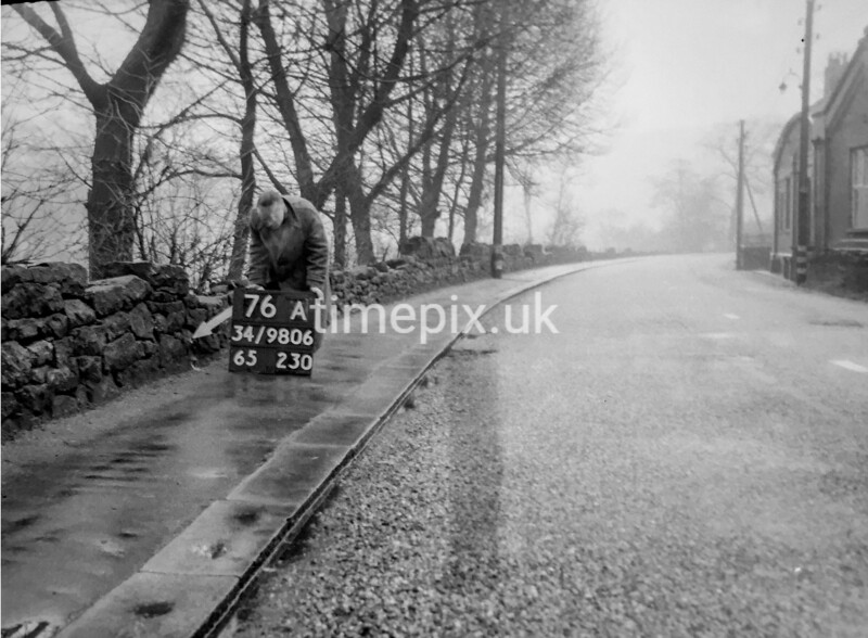 SD980676A, Man marking Ordnance Survey minor control revision point with an arrow in 1950s